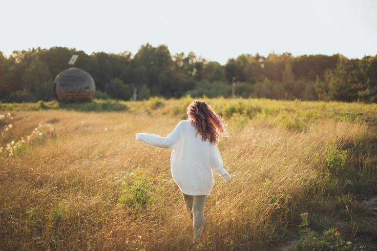 woman-wearing-white-jacket-while-walking-on-grass-field-3099675